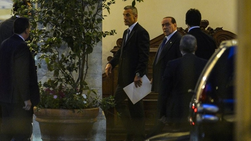Former Italian prime minister Silvio Berlusconi (2ndR) leaves his residence Palazzo Grazioli June 25, 2013 in Rome. Italy's top court begins crucial hearings for former prime minister Silvio Berlusconi on Tuesday that will decide whether to confirm a one-year prison sentence and a five-year ban from politics.