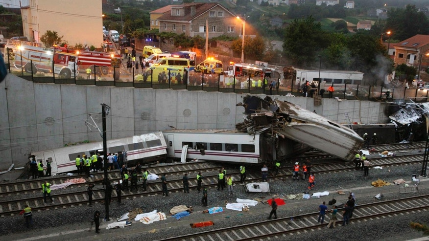 Emergency personnel respond to the scene of a train derailment in Santiago de Compostela, Spain, on Wednesday, July 24, 2013.