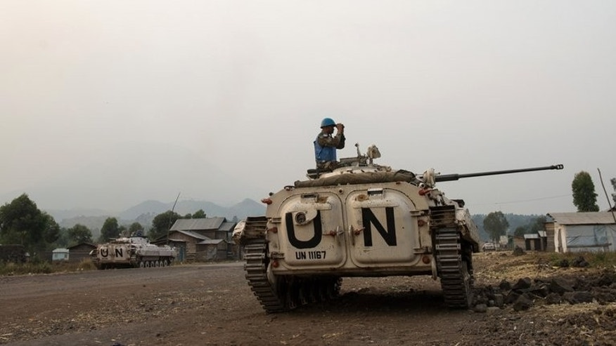 A United Nations peacekeeper looks through binoculars towards M23 positions in Kanyarucinya on the outskirts of Goma in the east of the Democratic Republic of the Congo on July 14, 2013. The UN threatened to use force against the M23 rebels, if they do not disarm within 48 hours.