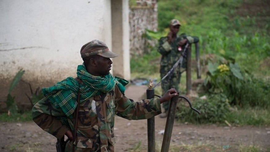 M23 rebels man the gate to the military academy in Rumangabo, in the east of the Democratic Republic of the Congo on July 20, 2013. The M23, a mainly Tutsi Congolese group founded in 2012, launched a new offensive against the DR Congo army outside Goma on July 14.