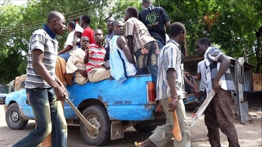 Machete and axe wielding vigilantes hop into a pick-up on July 19, 2013 to hunt down Boko Haram Islamists in Maiduguri. Young men and women have in recent weeks formed vigilante groups, hunting down Boko Haram Islamists.