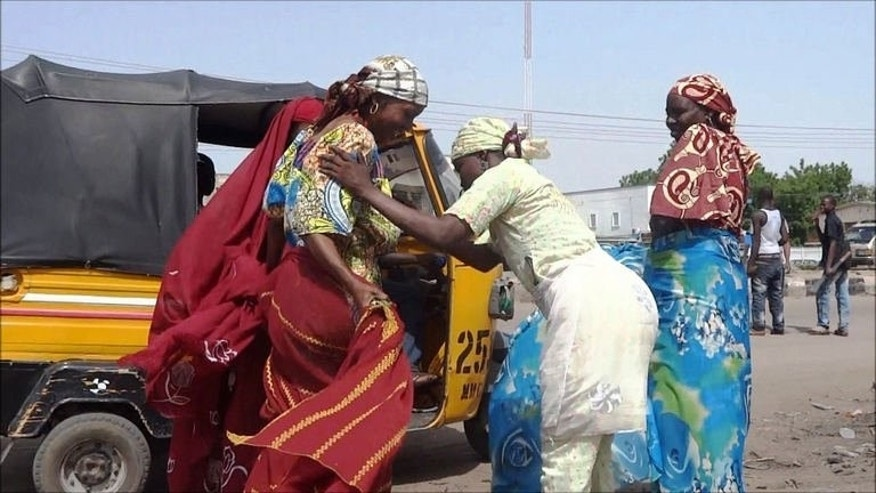 A female vigilante frisks two women passengers of a motorized rickshaw on July 19, 2013 in Maiduguri. Vigilante leaders say the force was formed following a gruesome June 11 attack by presumed Boko Haram members in Maiduguri's Hausari neighbourhood.