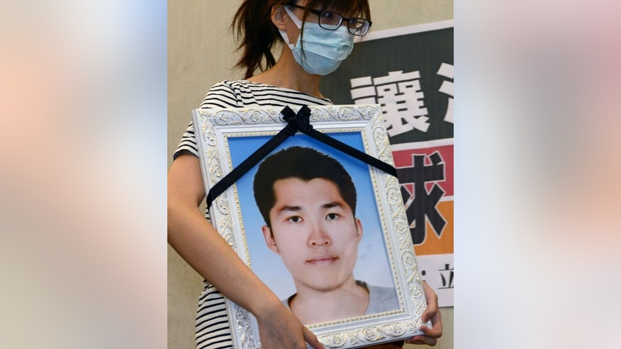 Hung Tse-yung holds a portrait of her brother during a press conference at parliament in Taipei, July 17, 2013. Corporal Hung Chung-chiu died of heatstroke on July 4, just three days before the end of his compulsory year-long military service. His family said he was forced to do excessive exercise as punishment for taking a smartphone onto his base.
