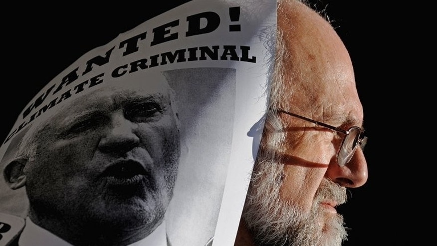 An environmentalist carries a poster condemning former New South Wales Mineral Resources and Energy Minister Ian Macdonald during a demonstration in Sydney on August 13, 2009. Macdonald has been accused of acting corruptly over a coal-mining deal.