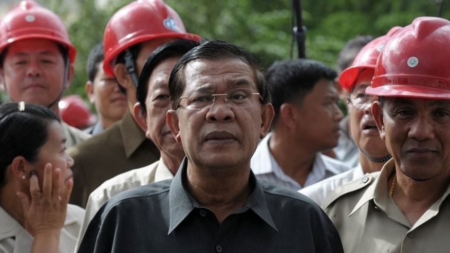 Cambodian Prime Minister Hun Sen (C) visits the construction site of a bridge in Phnom Penh on July 31, 2013. Hun Sen said Wednesday he would welcome any investigation into claims of fraud in hotly disputed polls and was open to dialogue with the opposition.