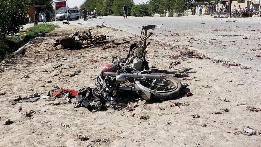 The wreckage of motorcycle lies at the site of a bomb blast in Aqcha district on July 25, 2013. Civilian casualties in the Afghan war rose 23 percent in the first half of this year due to Taliban attacks and increased fighting between insurgents and government forces, the UN said Wednesday.