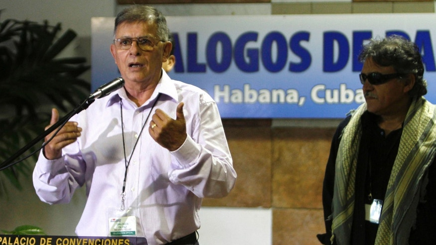 Ricardo Tellez, member of the Revolutionary Armed Forces of Colombia, or FARC, talks to reporters accompanied by Jesus Santrich, right, during peace talks with negotiators from Colombia's government in Havana, Cuba, Tuesday, July 30, 2013. Farc reiterates its willingness to free a former U.S. Marine it captured last month and insists that the government send a high-level commission to retrieve him. (AP Photo/Ismael Francisco, Cubadebate)