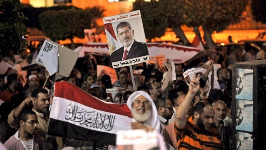 "Egyptian supporters of Mohamed Morsi hold his portrait during a demonstration against the government in Cairo, on July 31, 2013. Egypt's cabinet have tasked police to take ""necessary measures"" to end protests by supporters of ousted president Mohamed Morsi, terming them a national security threat."