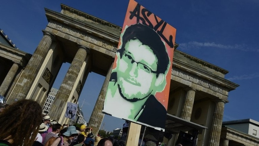 Demonstrators in Berlin, July 27, 2013, hold a placard showing US fugitive Edward Snowden during a protest against the US National Security Agency (NSA) collecting German emails, online chats and phone calls. Snowden's father reached out to his son on Russia's national television Wednesday, telling him he did not mind if the intelligence leaker stays in Russia as long as he is safe.
