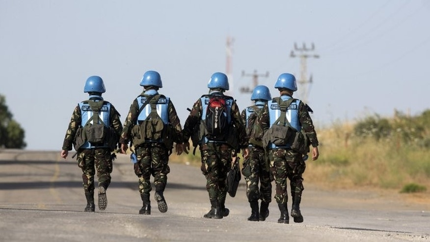 United Nations peacekeepers from the Philippines walk down a road in the Golan Heights on June 12, 2013. The Philippines said Wednesday it would likely keep its 340 soldiers in the Golan Heights as part of a United Nations peacekeeping force, amid improved security for the troops.