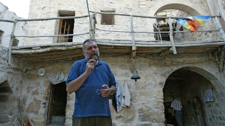 Father Paolo Dall'Oglio stands in a courtyard and talks to a visitor at Syria's historic Monastery of Mar Moussa, on July 11, 2007. Pope Francis has voiced concern over the fate of an Italian Jesuit priest missing in Syria.