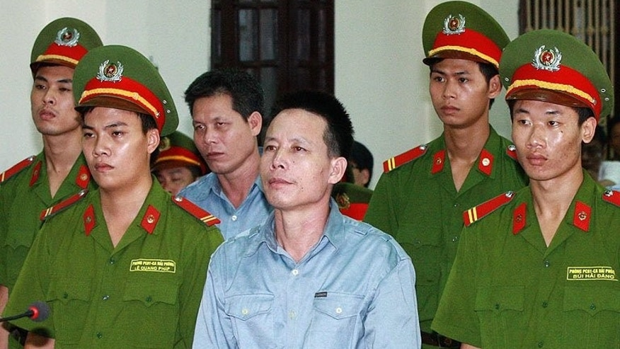 Vietnamese fish farmer Doan Van Vuon (centre, front row) listening to the verdict at the court in Hai Phong, on July 30, 2013. Vuon -- who became a folk hero after he used homemade weapons to resist forced eviction -- has lost his appeal against a five-year jail term for attempted murder.