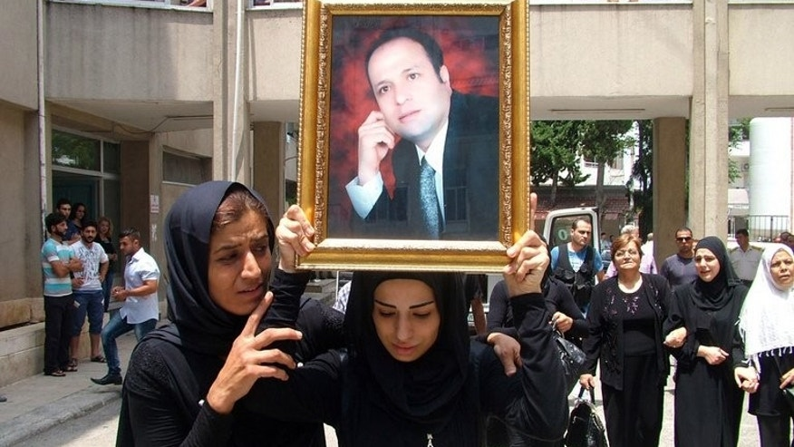 The daughter of Mohammad Darrar Jamo carries his portrait during his funeral in the Latakia province on July 19, 2013. The wife of the slain Syrian political analyst and ardent supporter of President Bashar al-Assad was charged in Lebanon on Wednesday with incitement to murder.