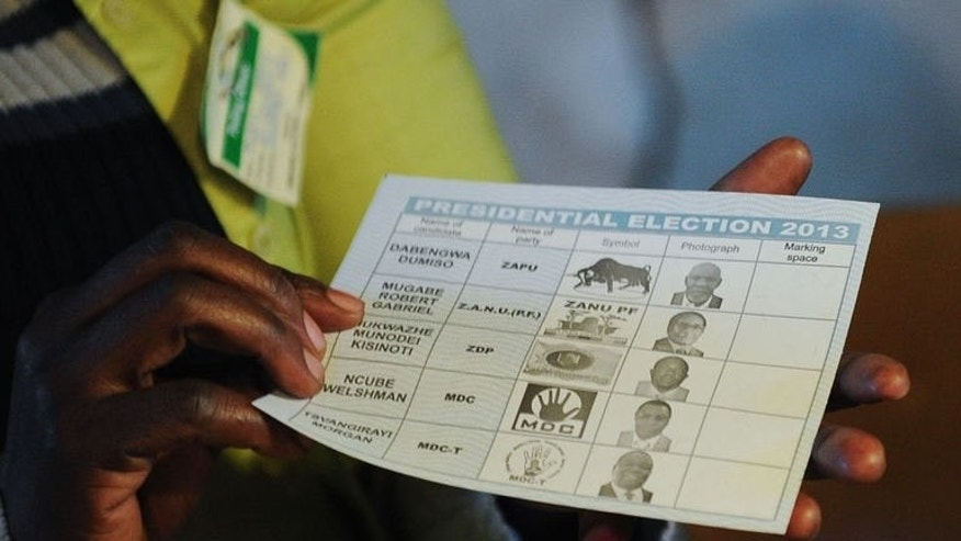 A Zimbabwean holds up a ballot at a polling station in Domboshava, 60km north of Harare, on July 31, 2013. Police in Zimbabwe on Wednesday warned they would arrest persons or groups that release unofficial results of the country's fiercely fought elections.