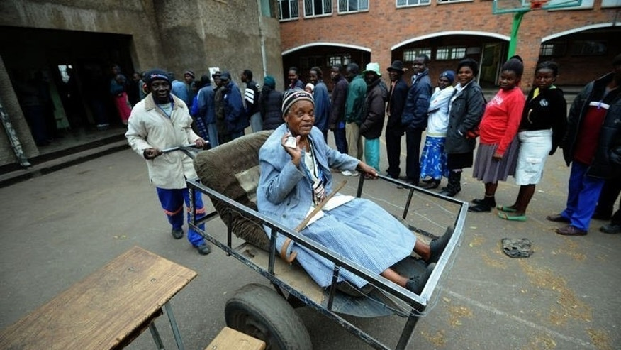 Zimbabwean Chizema Najika (L), 80, shows her card as she leaves in cart after voting at a polling station where other people queue up in Harare on July 31, 2013. Wrapped in blankets, Zimbabweans braved chilly weather Wednesday and turned up in droves to vote in a fiercely contested presidential election.