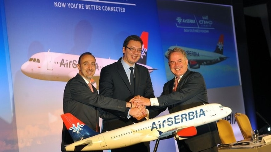 Air Serbia general manager Dane Kondic (left) shakes hands with Serbian Deputy Prime Minister Aleksandar Vucic (centre) and Etihad Airways president James Hogan after signing a partnership agreement in Belgrade, on August 1, 2013. Abu Dhabi-based Etihad Airways has signed an agreement with Serbia to acquire 49 percent of its loss-making JatAirways, which will be rebranded as Air Serbia.