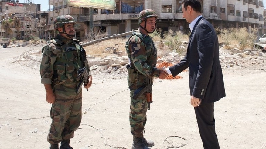 A handout picture released by the Syrian Arab News Agency (SANA) on August 1, 2013 allegedly shows Syrian President Bashar al-Assad shaking hands with a soldier in Daraya, southwestern of the capital Damascus.