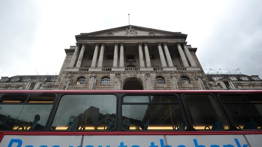 A bus passes the Bank of England in London. The Bank of England said on Thursday its policymakers had voted by a majority to keep its main lending rate at a record-low 0.50 percent.