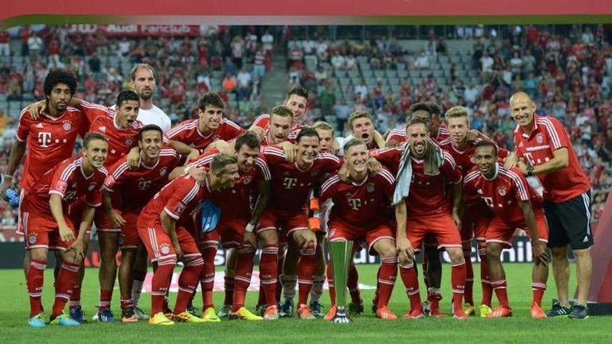 The team of FC Bayern Munich celebrate with the trophy after the Audi Cup football final match against Manchester City in Munich, southern Germany on August 1, 2013. Bayern Munich won the match 2-1.
