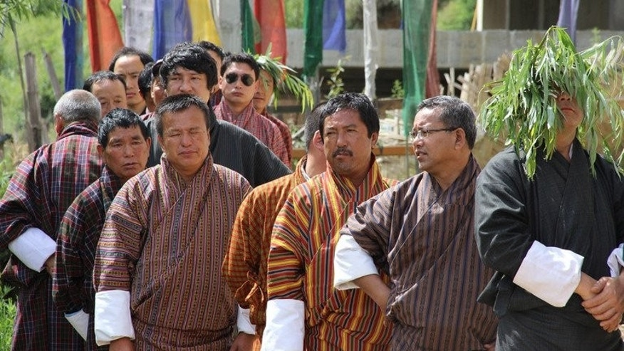 "Bhutanese men wait in line to cast their votes at a polling station in Thimphu, on July 13, 2013. Bhutan's pursuit of ""Gross National Happiness"" has brought it global fame as a model of alternative development, but its new prime minister believes the doctrine has distracted from tackling the country's problems."