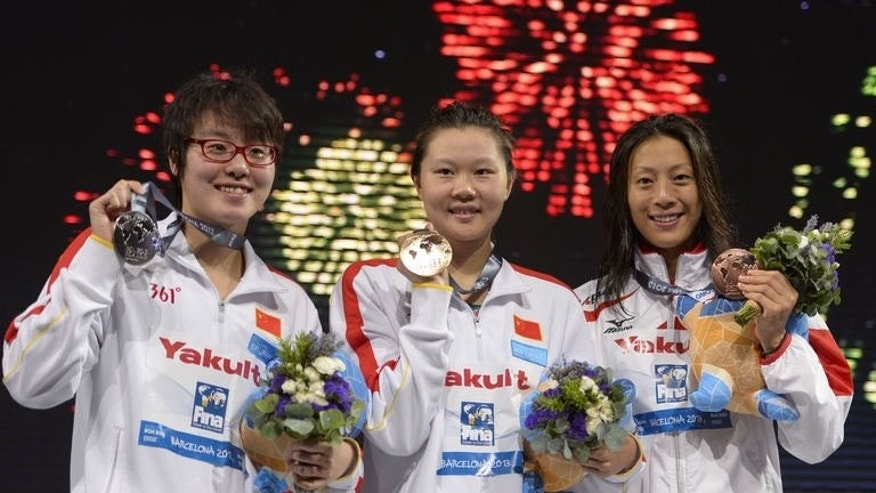 Gold medalist China's Zhao Jing (C), silver medalist China's Fu Yuanhui (L) and bronze medalist Japan's Aya Terakawa pose on the podium during the award ceremony of the women's 50-metre backstroke swimming event in the FINA World Championships at Palau Sant Jordi in Barcelona on August 1, 2013.