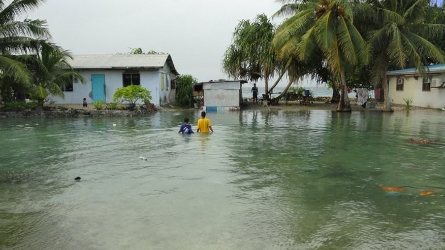 "Residents wade through flooding caused by high ocean tides in low-lying parts of Majuro Atoll, the capital of the Marshall Islands, on February 20, 2011. The Marshall Islands has warned of a Pacific ""climate catastrophe"" that will wipe it off the map without decisive action on global warming, saying the next 12 months are critical."