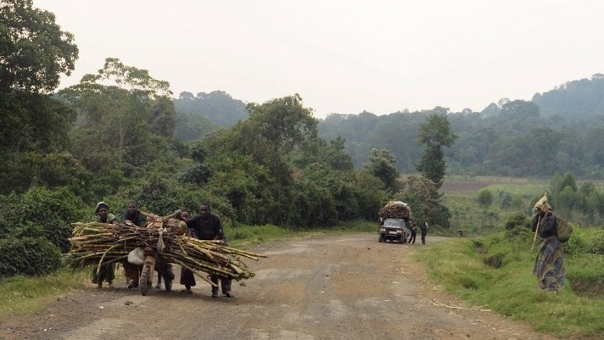 People walk on a road leading to the village of Kimbumba, in M23 rebel-held territory, in DR Congo on July 25. The United Nations on Tuesday threatened to use force against M23 fighters near Goma if they did not disarm within 48 hours.