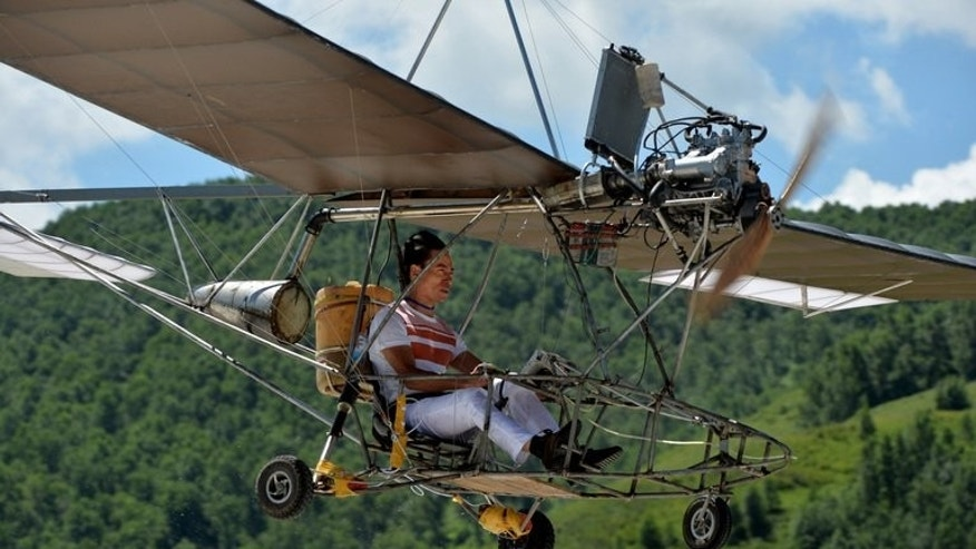 Wang Qiang flies his home-made plane during the Air Nadaam festival in Hexigten, Inner Mongolia on July 28, 2013. Wang spends his days trimming and shaping at a hair salon in Zhejiang province, and his evenings working on the one-seater craft.