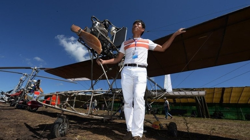 Wang Qiang stands beside his home-made plane at the Air Nadaam festival in Hexigten, Inner Mongolia on July 28, 2013. Wang's machine took eight months to build and cost 30,000 yuan ($5,000).