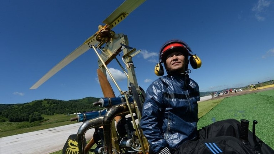 Shu Bin, a machine repairer from Zhejiang province, is seated in his home-made helicopter in Hexigten, Inner Mongolia on July 28, 2013. Around 20 private planes, microlights and motorised paragliders took to the air in a valley in Hexigten Banner at the weekend in the country's first festival of its kind.