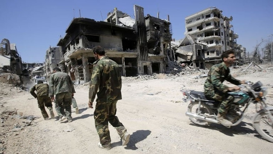 Syrian government forces patrol the Khaldiyeh district of Homs, on July 31, 2013. Buildings flattened like pancakes, roads filled with war debris, its famous mosque battle-scarred, the Syrian government's recapture of a rebel district of flashpoint Homs came at a high cost.