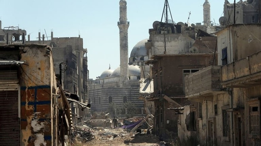 A Syrian tank is seen outside Khaled bin Walid mosque in the Khalidiyah district of Homs, on July 31, 2013. Buildings flattened like pancakes, roads filled with war debris, its famous mosque battle-scarred, the Syrian government's recapture of a rebel district of flashpoint Homs came at a high cost.