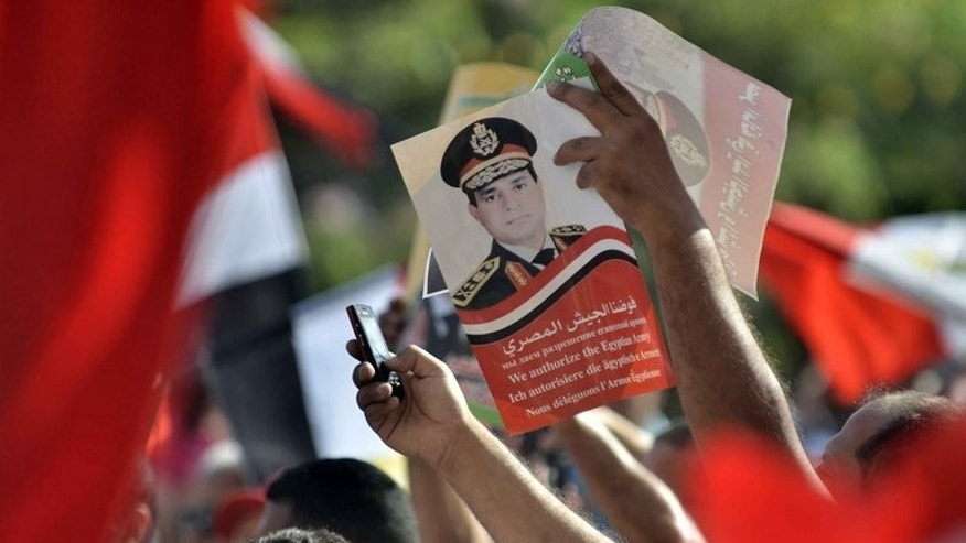 Egyptian opponents of deposed president Mohamed Morsi hold up a poster of army chief General Abdel Fattah al-Sisi on July 26, 2013 during a protest in Cairo. General Abdel Fattah al-Sisi's stern features look down from behind aviator sunglasses in photos on Egypt's front pages and from street posters, and there's already talk of a presidential run.