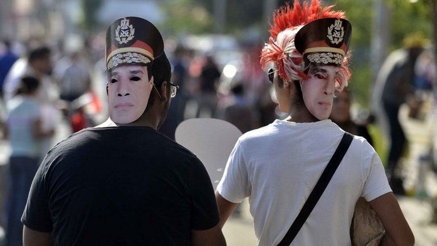 Egyptian opponents of deposed president Mohamed Morsi walk towards Tahrir Square in Cairo wearing cardboard cut-out masks of army chief General Abdel Fattah al-Sisi on July 26, 2013.