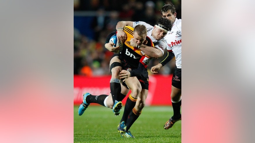 Robbie Robinson (C) of the Waikato Chiefs is tackled during a Super 15 match in Hamilton on August 4, 2012. The Chiefs have been forced to prepare an alternative combination with fullback Robinson on standby for the wing berth.