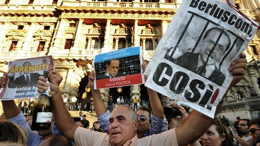 A man holds a poster and a champagne bottle as people celebrate in Rome, on August 1, 2013 after the Supreme Court handed former prime minister Silvio Berlusconi his first ever definitive conviction in a 20-year political career that has been dogged by legal woes and sex scandals.