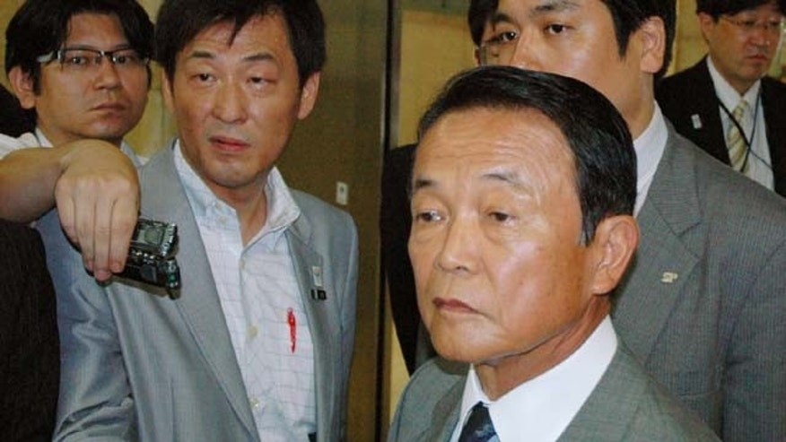 August 1, 2013: Japanese Finance Minister Taro Aso (foreground) is surrounded by reporters at the ministry in Tokyo. Aso has retracted a comment he made Monday suggesting Japan should learn from how the Nazi party stealthily changed Germany's constitution before World War II before anyone realized it. (AP Photo)