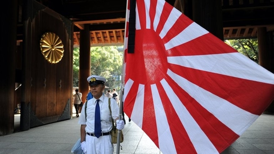 A worshipper stands with a Rising Sun flag while entering the controversial Yasukuni shrine in Tokyo, on August 15, 2011. Japanese Prime Minister Shinzo Abe will not visit a controversial shrine to war dead on the anniversary of his country's surrender in World War II, AFP sources and a report said Thursday.