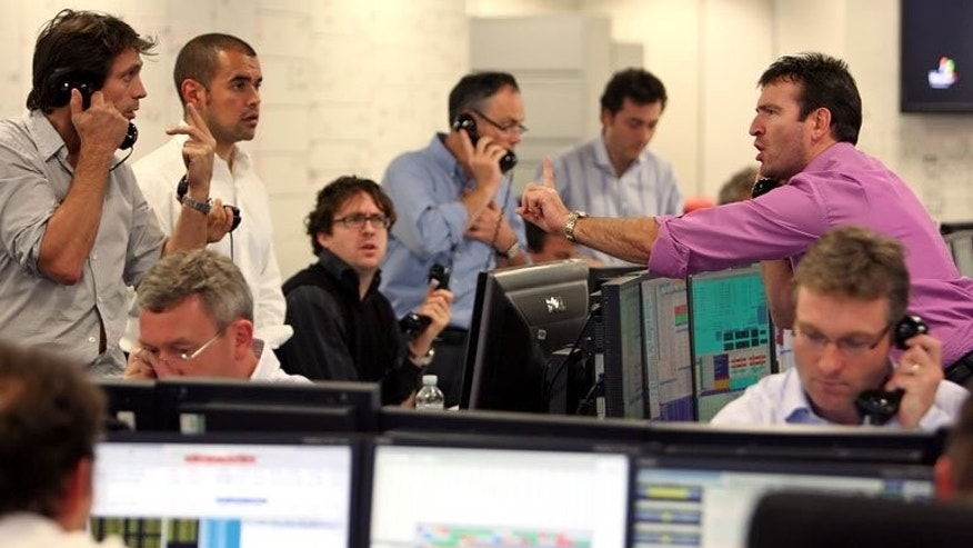 Brokers on the dealing floor at ICAP in London. London shares opened higher on Thursday as BAe Systems and Lloyds Banking Group rose after results, though gains were restricted by a sharp fall in Shell after the oil giant revealed a plunge in net profit.