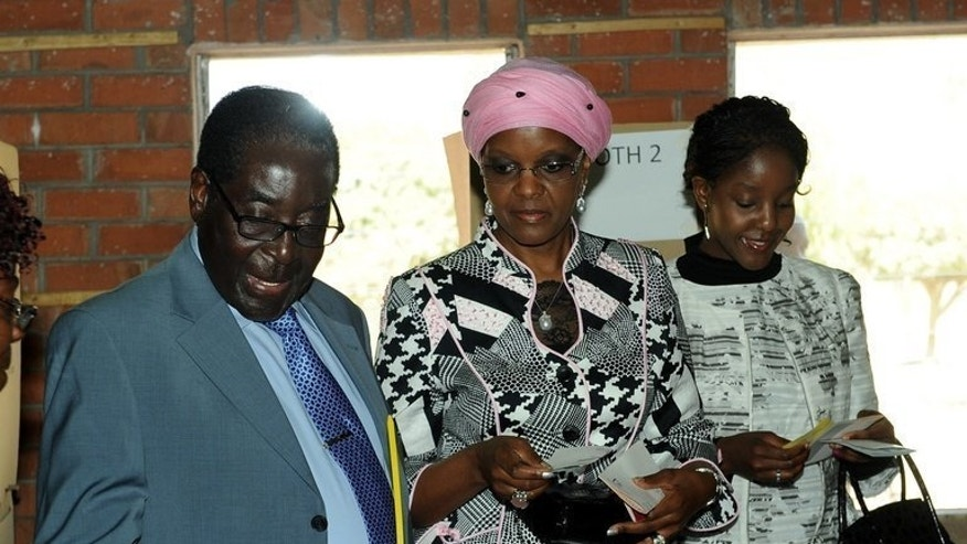 "Zimbabwe President Robert Mugabe casts his vote at a polling station in Harare, on July 31, 2013. Zimbabwean President Robert Mugabe's allies declared Thursday that the veteran leader had romped to an election victory, a claim rejected by his rival who branded the vote a ""sham."""
