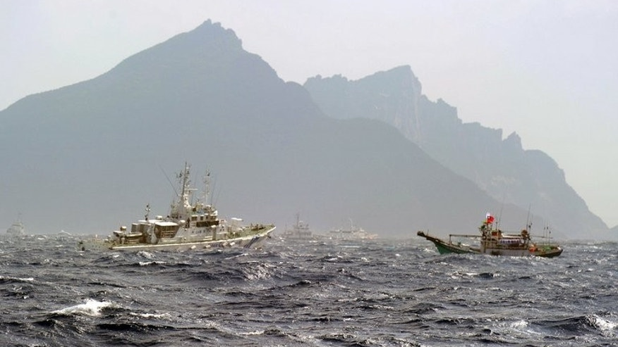 A Taiwan fishing boat (R) is blocked by a Japan Coast Guard (L) vessel near the disputed Diaoyu / Senkaku islands in the East China Sea on September 25, 2012.