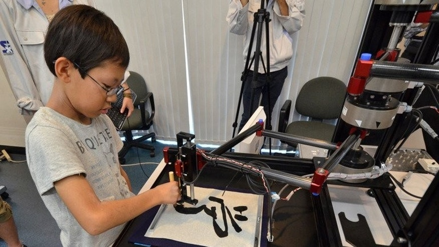 """A boy writes a Chinese letter for """"study"""" with a calligraphy robot at Keio University in Yokohama on July 30, 2013. The motion copy robot can recreate master works and the users can experience the same pressure and the same gestures of brush works by master painters or calligraphers."""