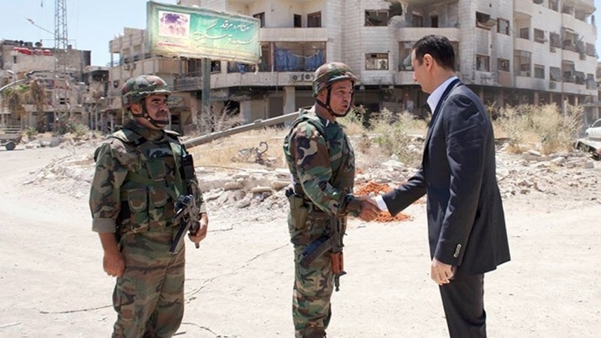 Aug. 1, 2013: This image posted on the official Facebook page of the Syrian Presidency purports to show Syrian President Bashar Assad shaking hands with a solider during Syrian Arab Army day in Daraya, Syria. Syrian state-run TV says Assad has visited a tense Damascus suburb to inspect his troops on the occasion of the country's Army Day. The visit on Thursday is Assad's first known public trip outside the capital, his seat of power, since he visited the Baba Amr district in the central city of Homs after troops seized it from rebels in March 2012.