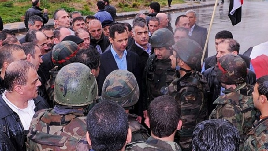 UNDATED: This photo posted on the official Instagram account of the Syrian Presidency purports to show Bashar Assad visiting with soldiers in Baba Armr, Homs province, Syria, in 2012.