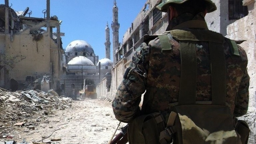 "A soldier loyal to the regime forces stands in front of the damaged Khaled bin Walid mosque in Homs, on July 29, 2013. Syrian President Bashar al-Assad said he was ""sure of victory"" over rebels fighting to topple him, in an Army Day message carried by state media."