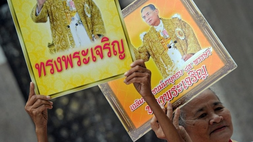 Thai well wishers hold portraits of Thai King Bhumibol Adulyadej in Bangkok on May 5, 2013. Thailand's frail king is expected to leave hospital and travel to his coastal palace on Thursday after almost four years as an in-patient, a government official said.