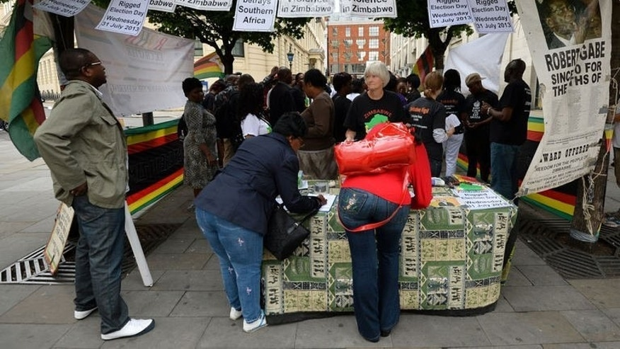 People sign a petition calling for a fair election outside the Zimbabwean Embassy in central London, on July 31, 2013. Zimbabwe's disputed election has plunged the country back into a deep political crisis and could open the way for decades more of autocratic rule.