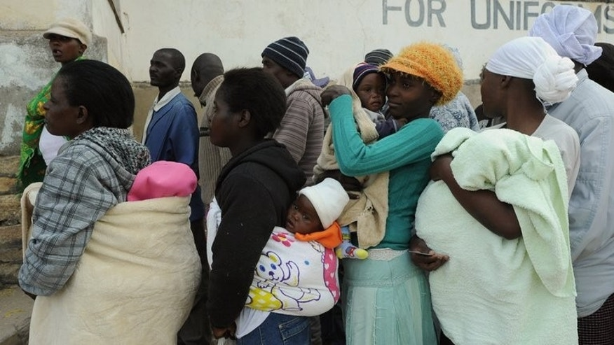 "Zimbabweans wait in line to cast their ballots at a polling station in Domboshava, 60km north of Harare, on July 31, 2013. Regional observers said Zimbabwe's election was ""orderly and fair"" despite charges of vote-rigging by allies of veteran President Robert Mugabe as vote counting got underway Thursday."