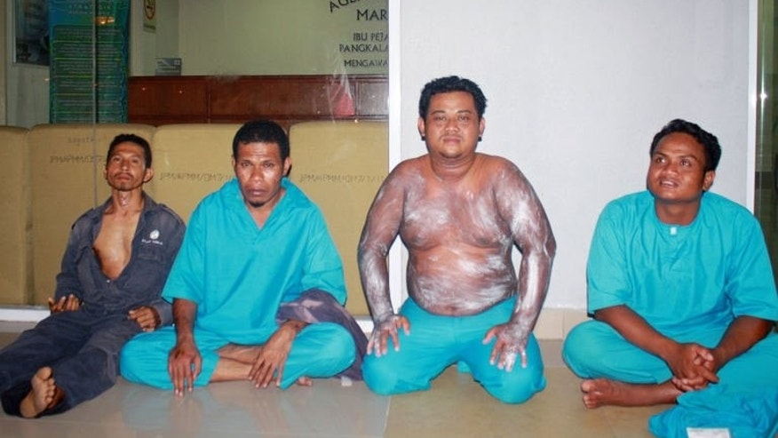 Image provided by the Malaysian Maritime Enforcement Agency shows passengers rescued from an overturned boat off the Johor coast wait at the maritime office on August 2, 2013. Forty Indonesians believed to be illegal immigrants seeking to return home went missing after a boat carrying them sank off the coast of Malaysia, a maritime official said on August 3.