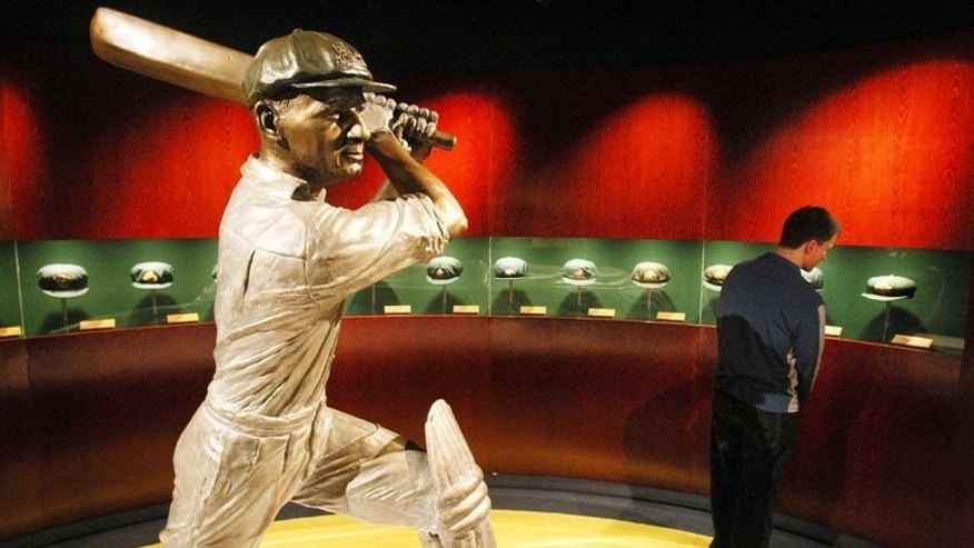 "A statue of Australian cricketing great Don Bradman is ringed by Baggy Green caps worn by the famous cricketer, at the Sports Museum at the MCG in Melbourne, on June 2, 2008. A bat used by Bradman and signed by his 1948 ""Invincible"" team is expected to fetch up to Aus$20,000 at auction this month, an auctioneer said on Friday."